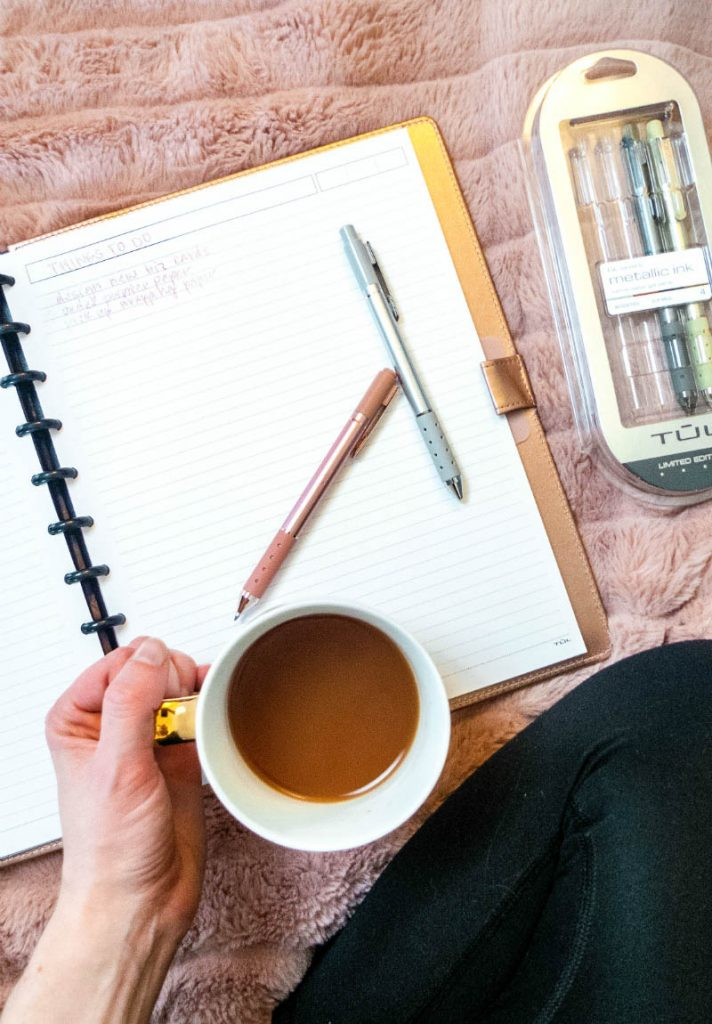 Notebook with pens and holding mug of tea