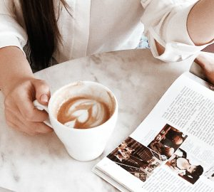 Girl holding a mug of coffee on a marble table