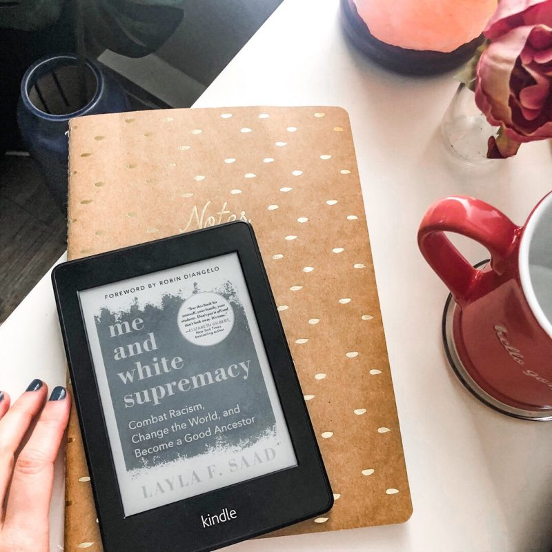 Photo of a Kindle with the book cover showing 'Me and White Supremacy'