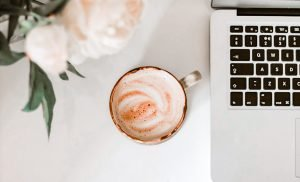 Desk with roses, latte, and laptop